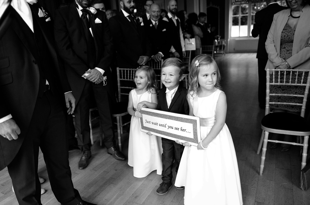 Grinning children excitedly reach the end of the aisle of the Orchid Room at Surrey wedding venue Nonsuch Mansion with their funny signboard heralding the arrival of the Bride