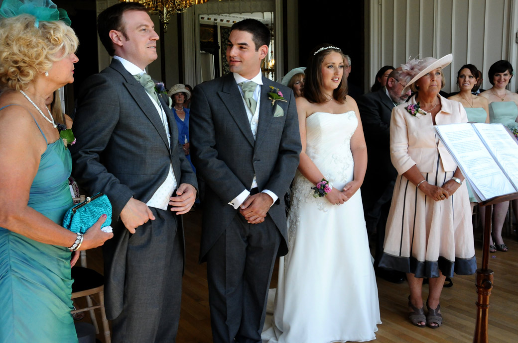 A mischievous Bestman pretends to have difficulty in finding the wedding rings in this humourus wedding photo from Surrey wedding venue Nonsuch Mansion