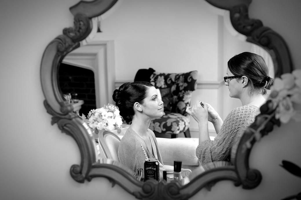 A through the mirror wedding picture of the Bride having her make up applied as she prepares for her Nonsuch Mansion wedding ceremony in Cheam Surrey