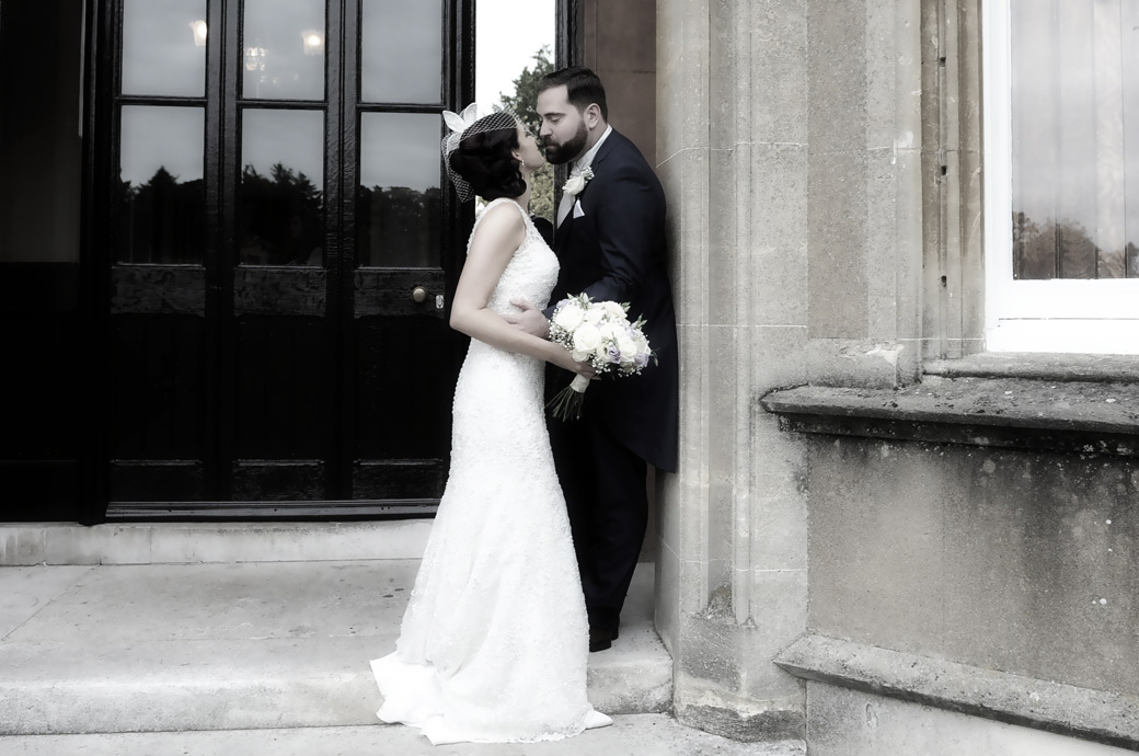 Newlyweds captured in this romantic wedding photograph ready for a kiss at Surrey wedding venue Nonsuch Mansion in Cheam as they lean against a wall