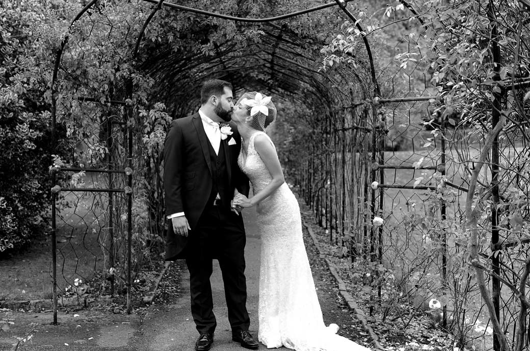 Newlywed couple take a dramatic and romantic pose in this touching Nonsuch Mansion wedding photograph taken in Surrey as they kiss in the rose walk