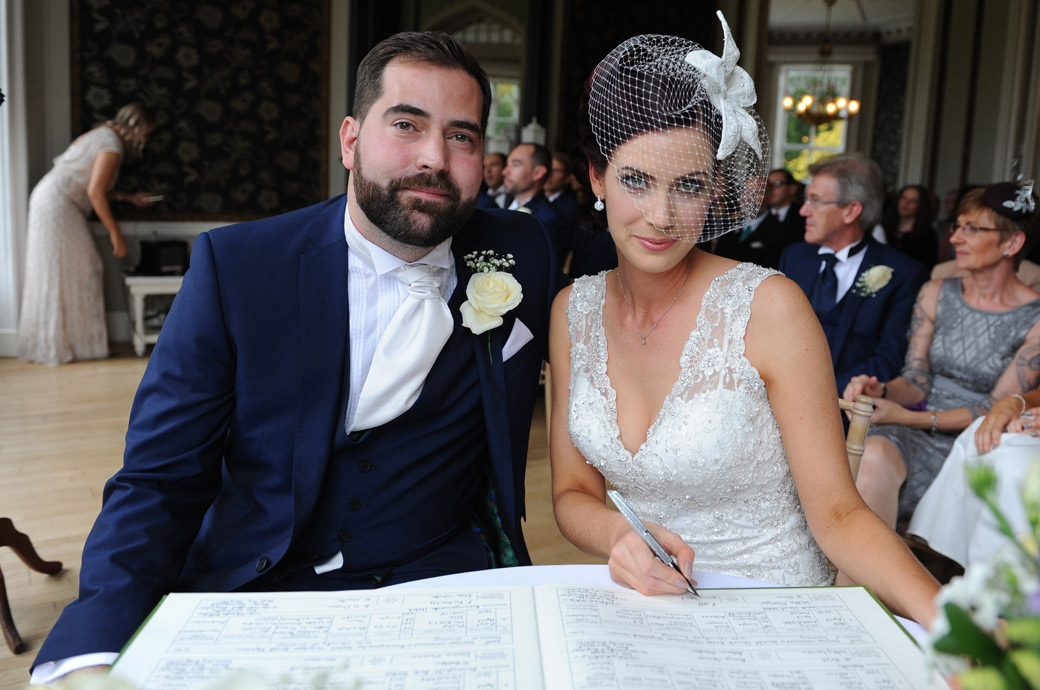 Handsome newlywed couple captured in this wedding picture taken in the Orchid Room in Surrey wedding venue Nonsuch Mansion as they sign the marriage register