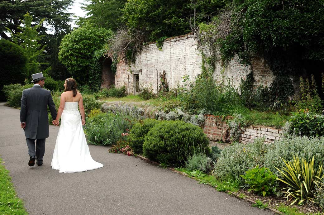 Romantic wedding photograph of a newlywed couple on a path holding hands as they walk towards the old boundary wall at Nonsuch Mansion in Cheam Surrey