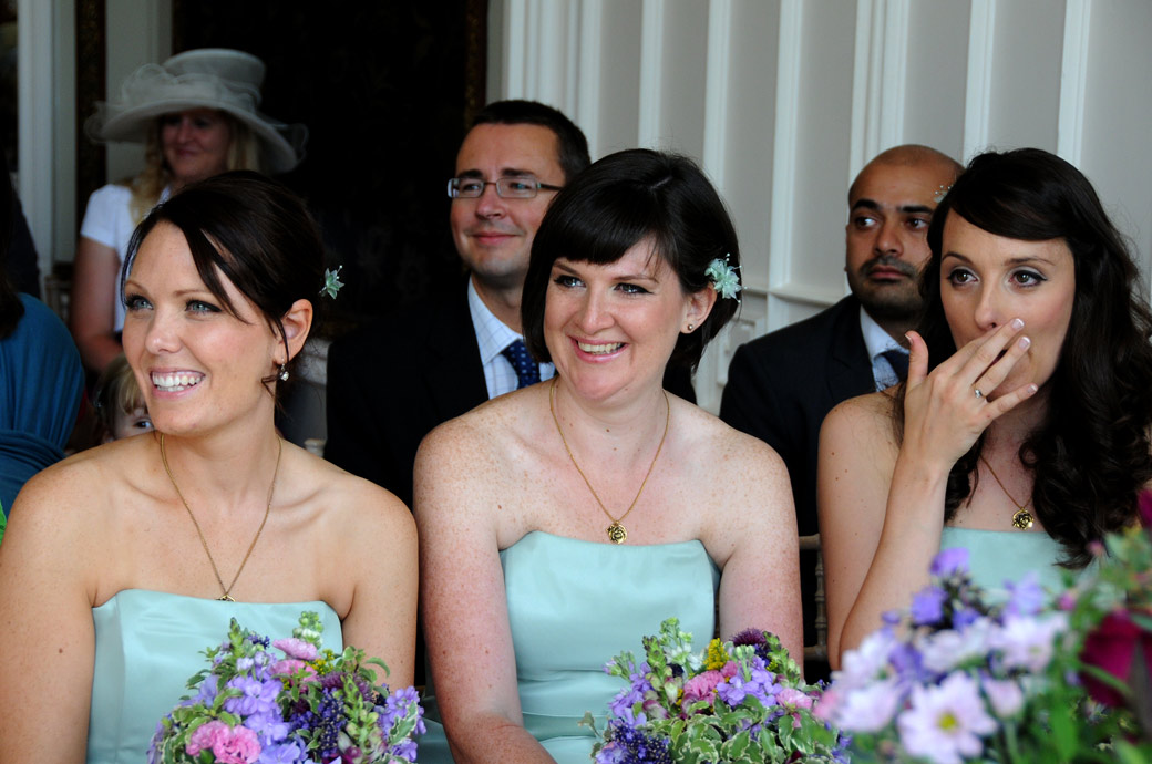Laughter and emotion in this Bridesmaids front row wedding photo captured at Nonsuch Mansion by Surrey Lane wedding photographer