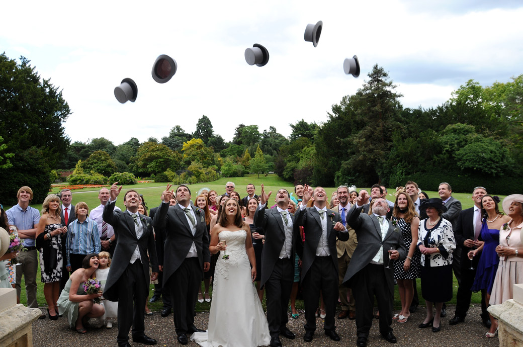 Amusing, fun wedding photo of Groomsmen throwing their top hats into the air on the lawn at Nonsuch Mansion Cheam by Surrey Lane wedding photography