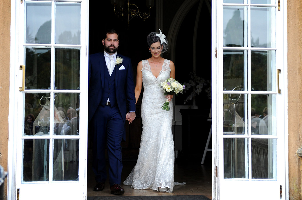 Wedding photo of a proud Groom escorting his beautiful Bride to the door to go out onto the terrace to meet their guests at Nonsuch Mansion in Cheam Surrey