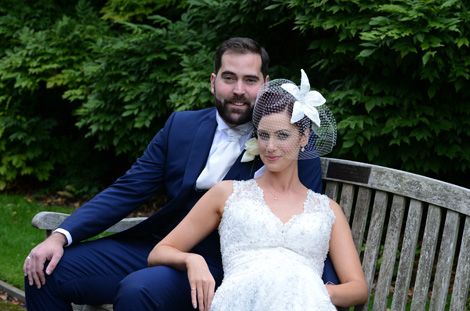 Smiling handsome newlywed couple captured in this wedding picture taken in Surrey at Nonsuch Mansion as they relax on a park bench after a romantic walk in the grounds