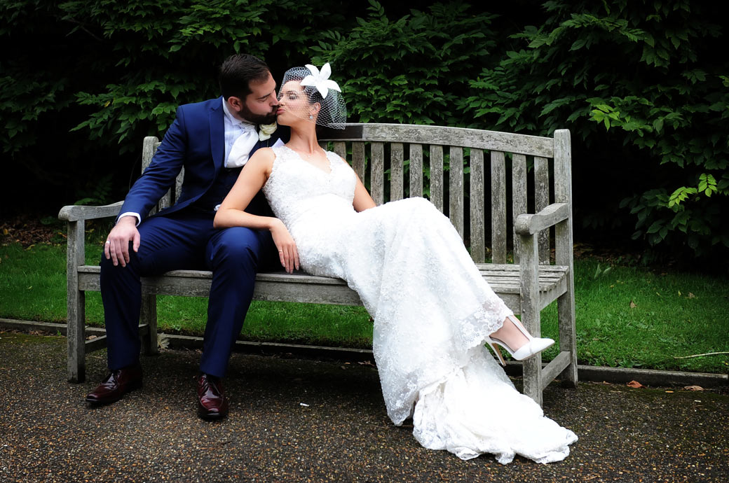 Wedding photograph of a romantic kiss on a park bench taken in leafy Surrey in the village of Cheam at the historic Nonsuch Mansion wedding venue