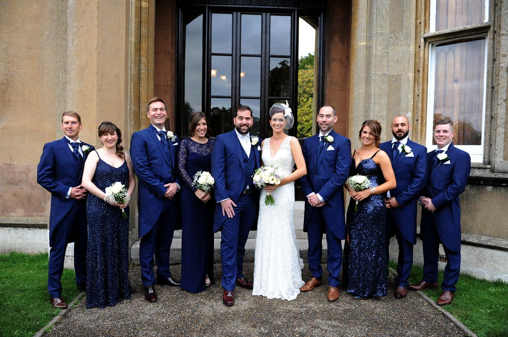 Bride and Groom with their groomsmen and bridesmaids all dressed in blue in this group wedding photo taken at Nonsuch Mansion a stunning Surrey wedding venue