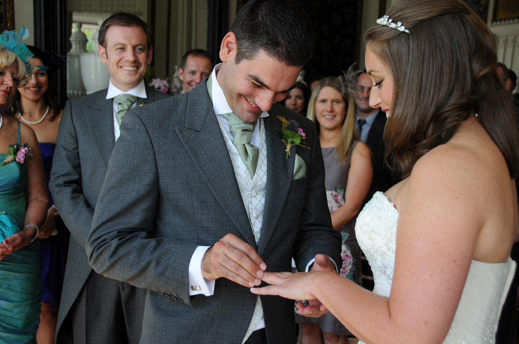 View an intimate wedding picture of a smiling groom trying to fit the ring on his bride's finger at Nonsuch Mansion by Surrey Lane wedding photography