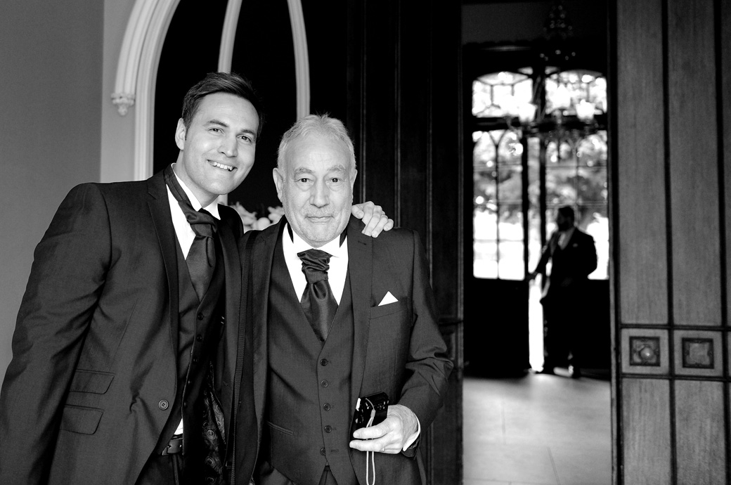 Father and brother of the Groom pose for a quick wedding photo outside the Orchid Room at Nonsuch Mansion a wedding venue in Surrey Cheam