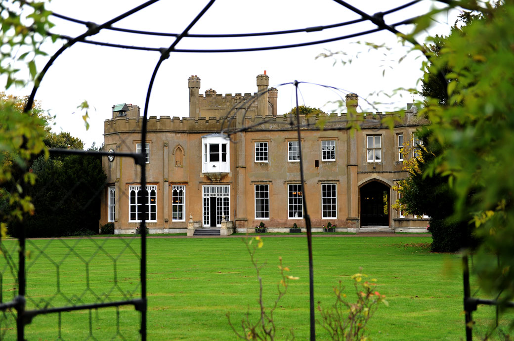 The distinctive sandy brown castellated Surrey wedding venue Nonsuch Mansion  as seen in this wedding photograph taken across the lawn from the Rose Walk