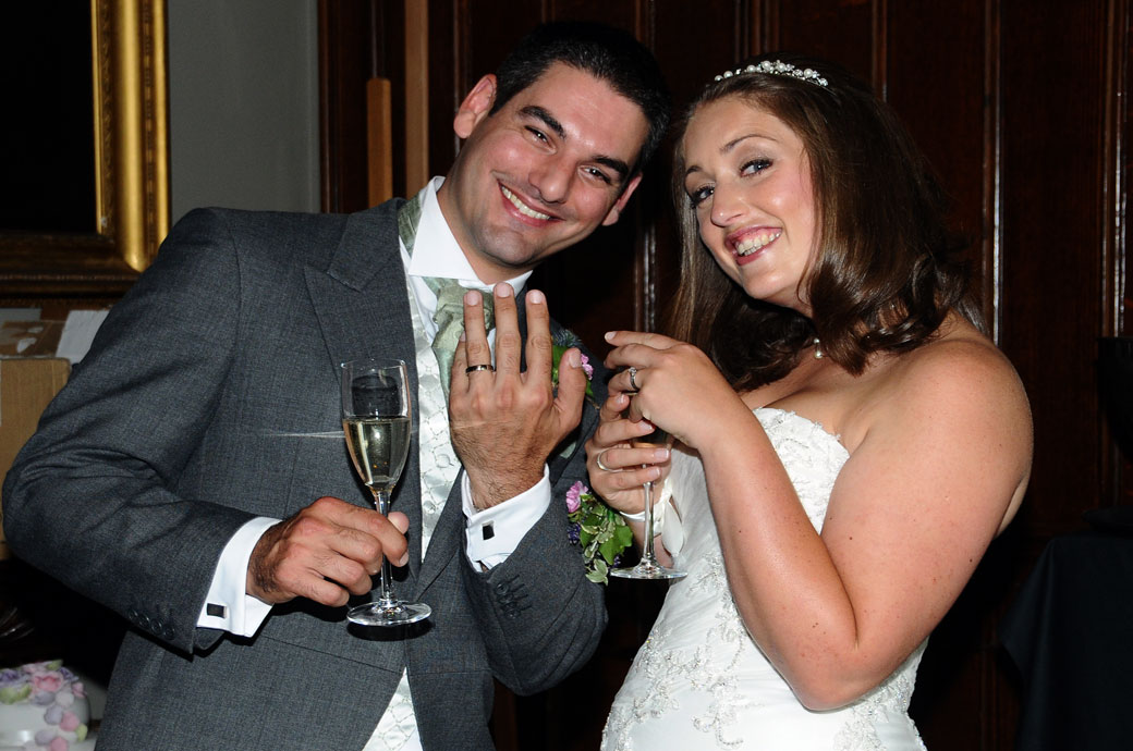 All smiles and wedding rings as the newly-weds with champagne in hand get ready to celebrate at the lovely Surrey wedding venue Nonsuch Mansion