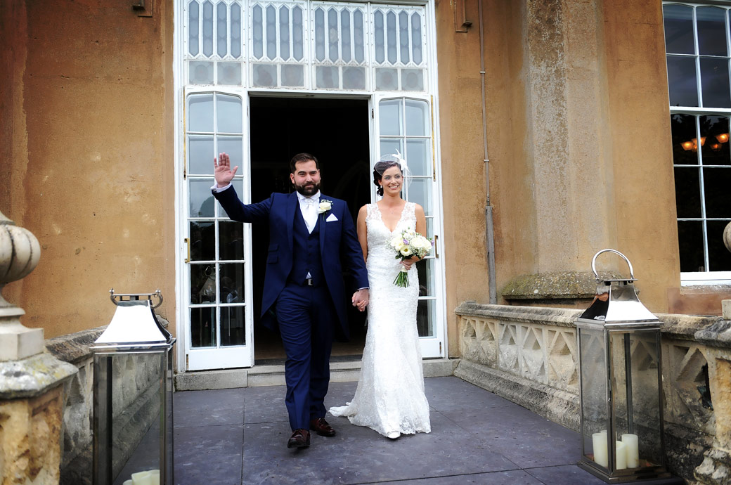 Groom waves a hand and his Bride smiles as they walk out onto the terrace to meet the guests on the lawn at Nonsuch Mansion in Cheam captured by a Surrey Lane wedding photographer