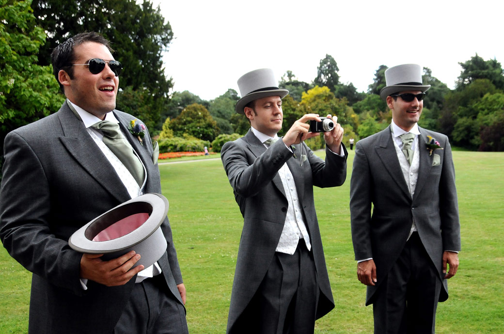 Groom and Groomsmen watch the fun in their top hats and sunglasses on the lawn at the wonderful Nonsuch Mansion wedding venue  in Cheam Surrey