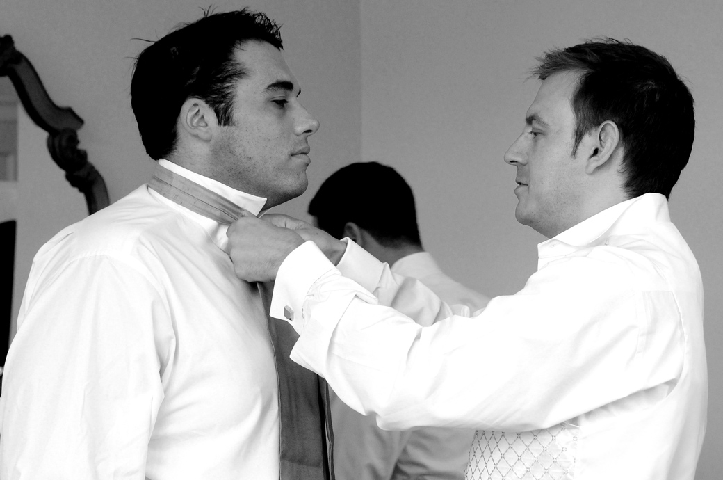 Groomsman helping another groomsman with his tie as the gents get ready on the morning of the wedding at Nonsuch Mansion in Cheam Surrey