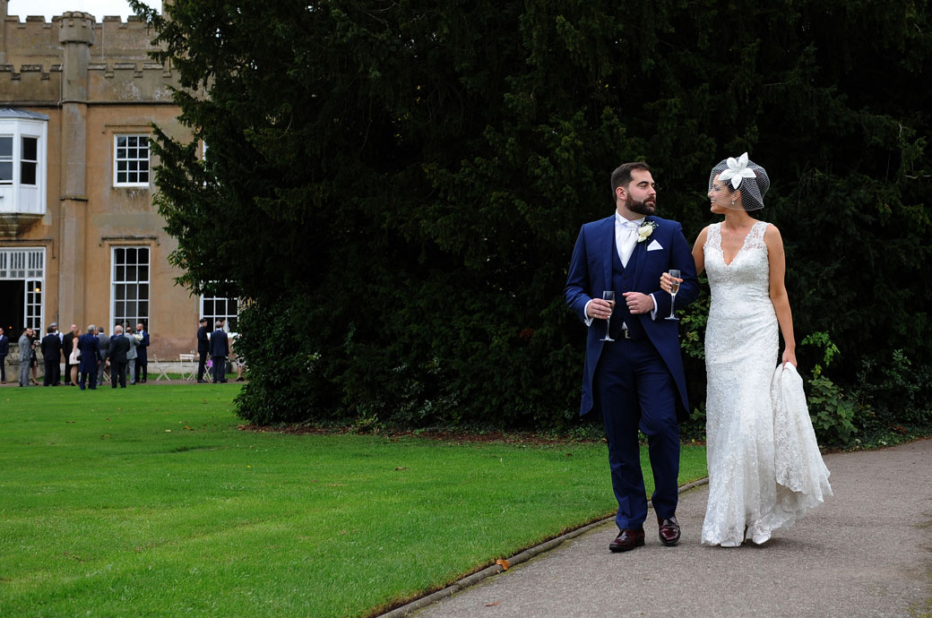 Romantic wedding photograph of newlyweds walking arm in arm champagne hand in hand and looking into each other's eyes at Nonsuch Mansion in Cheam Surrey