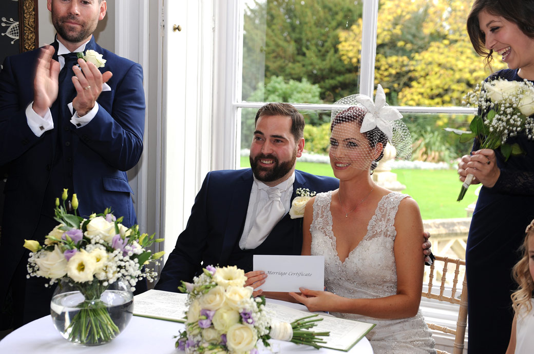 Smiling Bride and Groom pose with their marriage certificate for the guests in the post wedding picture taken at the historic Surrey wedding venue Nonsuch Mansion