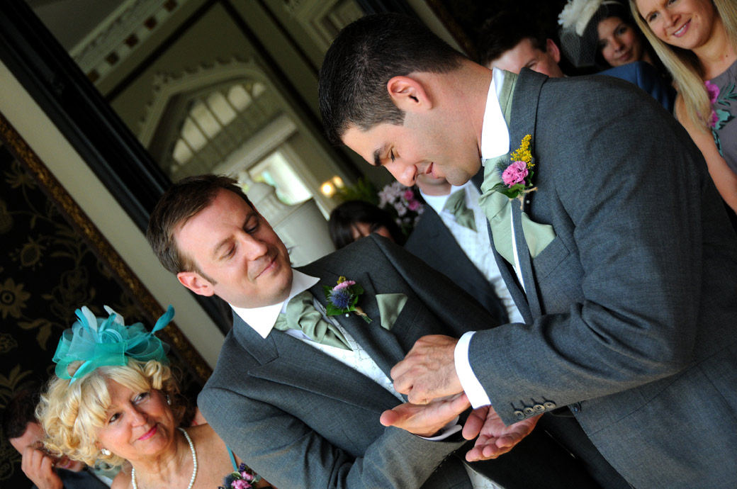 Mischievous Bestman offers the wedding ring to a smiling Groom in this fun wedding photograph taken at Surrey wedding venue Nonsuch Mansion