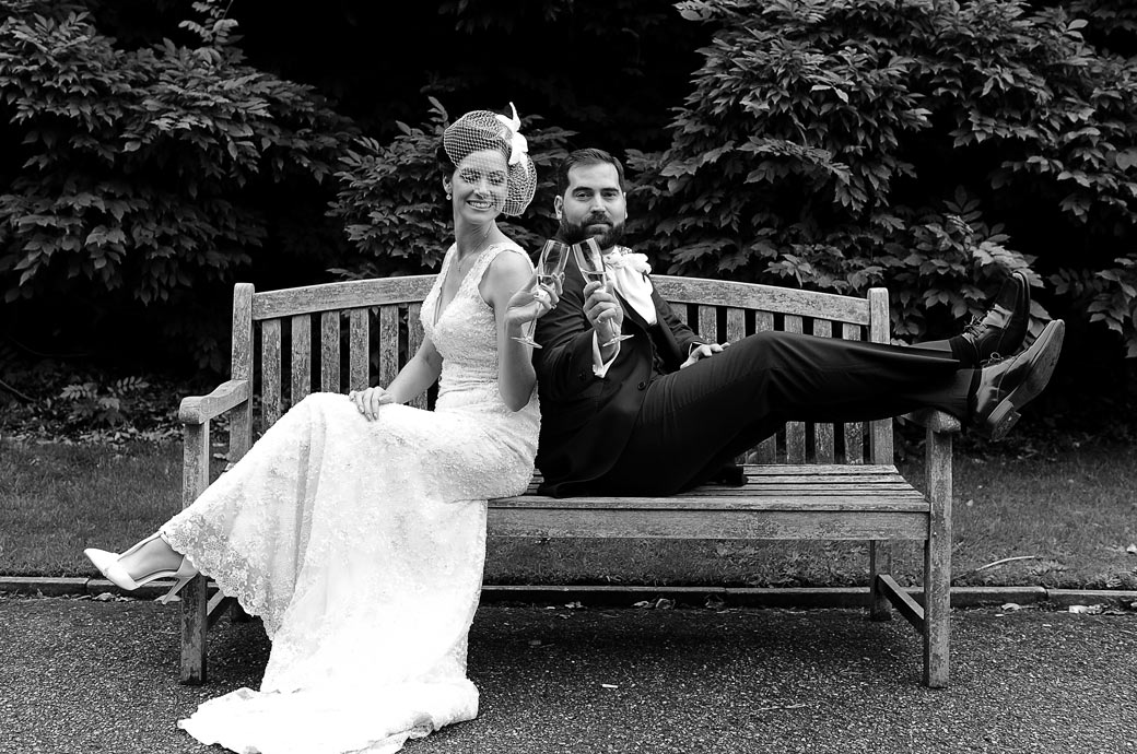 Bride and groom clink their champagne glasses together in this wedding photo taken at Nonsuch Mansion in Cheam Surrey as they sit with legs up on a garden bench