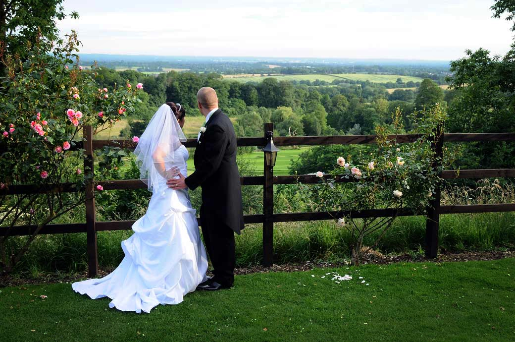 A beautiful scenic wedding photo of a Bride and Groom looking over the South Downs from the magnificent Surrey wedding venue Nutfield Priory, Redhill