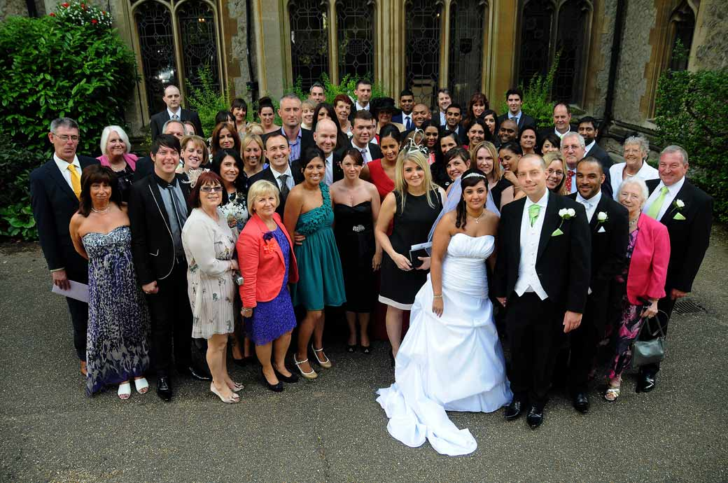 Happy smiling everyone at the wedding photograph taken at the front of the grand Nutfield Priory Redhill captured by Surrey Lane wedding photography
