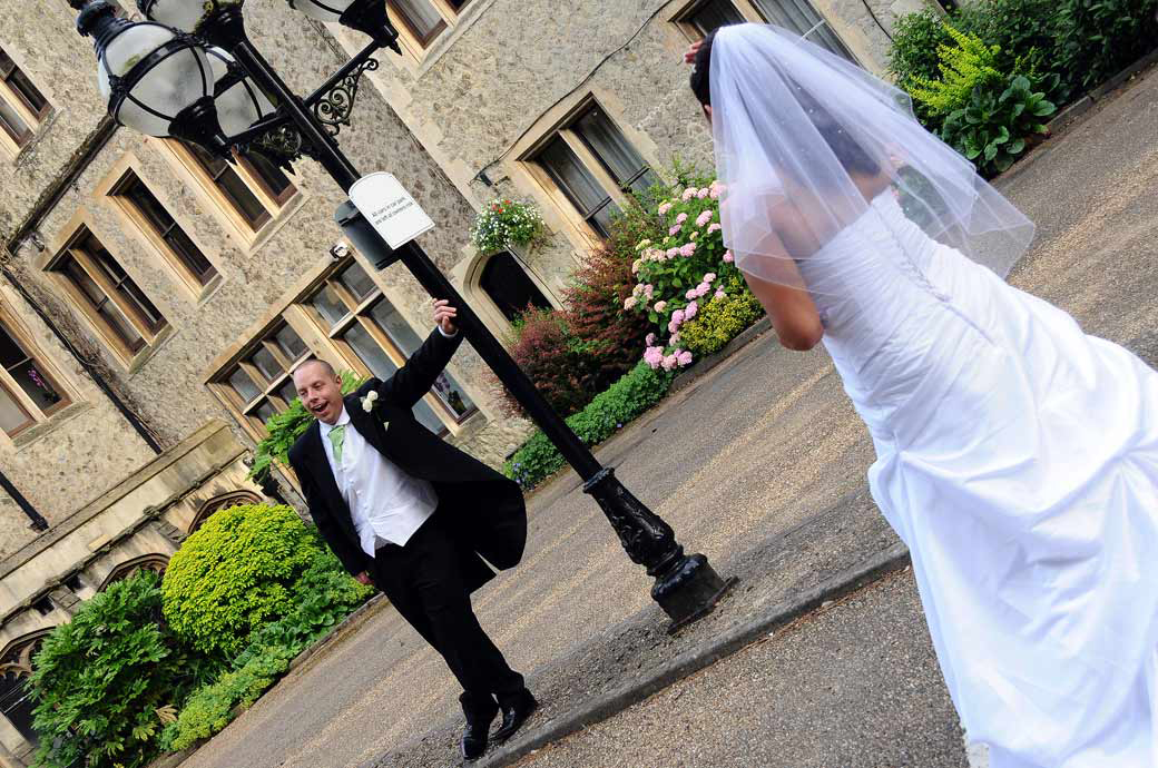 Funny Groom yawning wedding picture as he leans against the lamppost at the impressive Neo-Gothic Nutfield Priory taken by Surrey Lane in Redhill