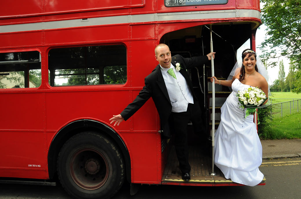 Bride and Groom leaning out of a double decker bus wedding photograph on their way to the grand Nutfield Priory, a Surrey wedding venue in Redhill