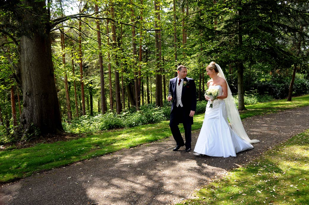 A beautiful woodland scene of the Bride and Groom looking at each other, champagne glasses in hand as they walk  down a path at Painshill Park Cobham