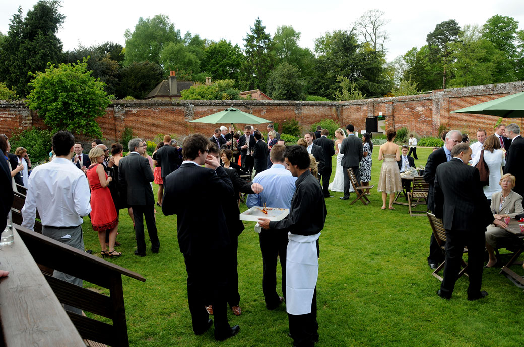 A picture of wedding guests having pre-wedding breakfast drinks in the enclosed Walled Garden reception area at Painshill Park in Cobham Surrey