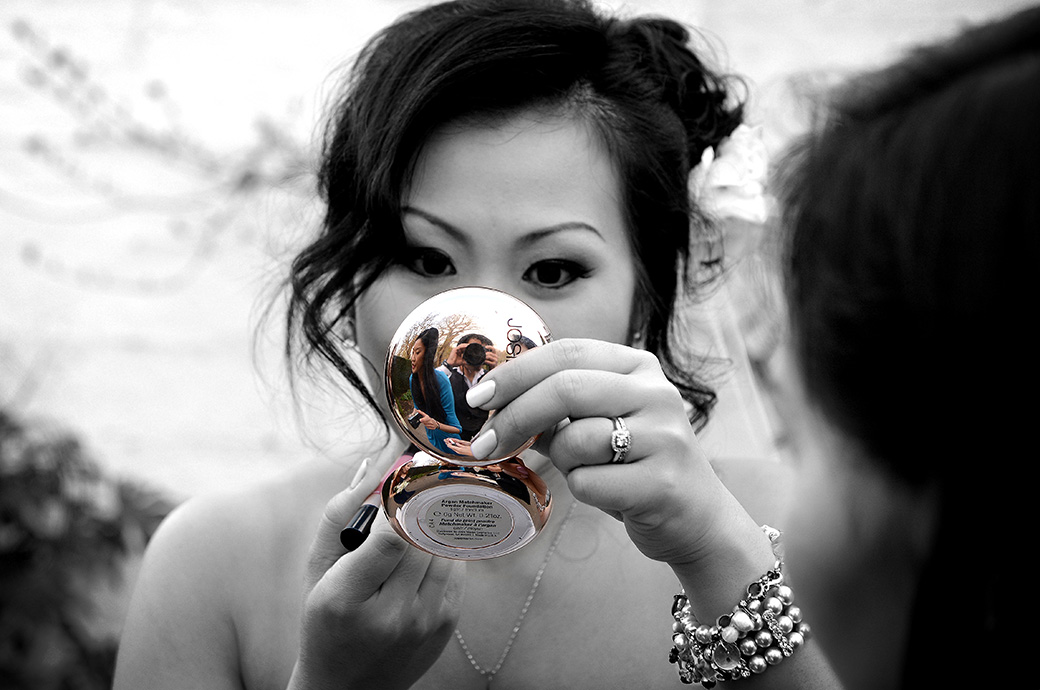 A Bride captured in this interesting looking wedding photo taken on the lawn at Pembroke Lodge in Richmond Park Surrey during the drinks reception as she applies some top up lipstick