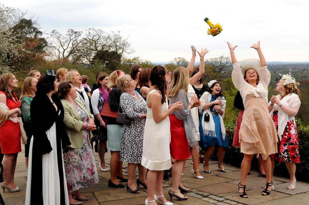 Colour fun wedding photo of ladies outstretched hands and smiling faces as they watch the Bride's bouquet fly through the air at Pembroke Lodge