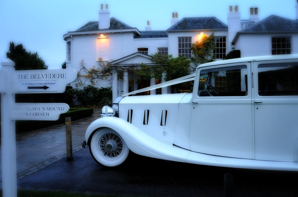 A beautiful Classic white wedding car photograph taken at dusk outside Pembroke Lodge wedding venue and captured by Surrey Lane wedding photography