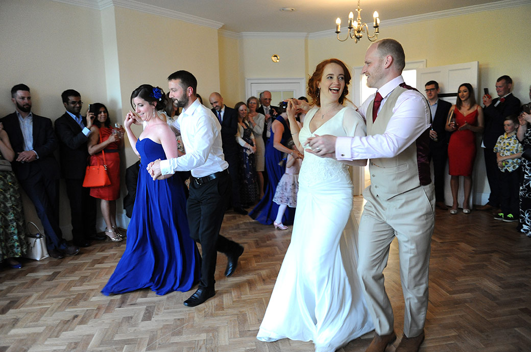 Bride and groom in full flow as they enjoy themselves along with guests in dancing a ceilidh at Pembroke Lodge in Richmond Park captured by a Surrey Lane wedding photographer