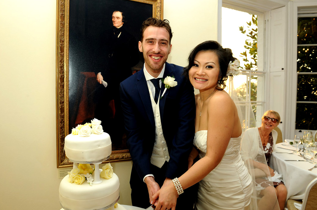Pembroke Lodge newlywed couple have fun cutting the wedding cake captured in this Surrey wedding picture taken in the intimate Russell Suite of this fine venue