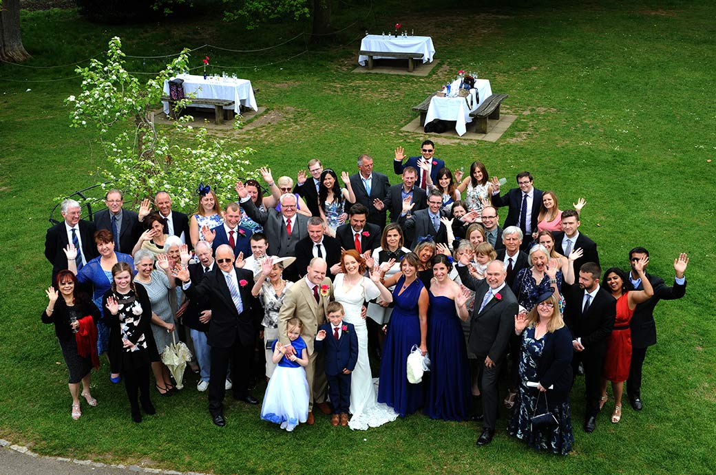 Everyone at the popular and lovely Surrey venue Pembroke Lodge looking up and waving at the Surrey Lane wedding photographer leaning out of the first floor window