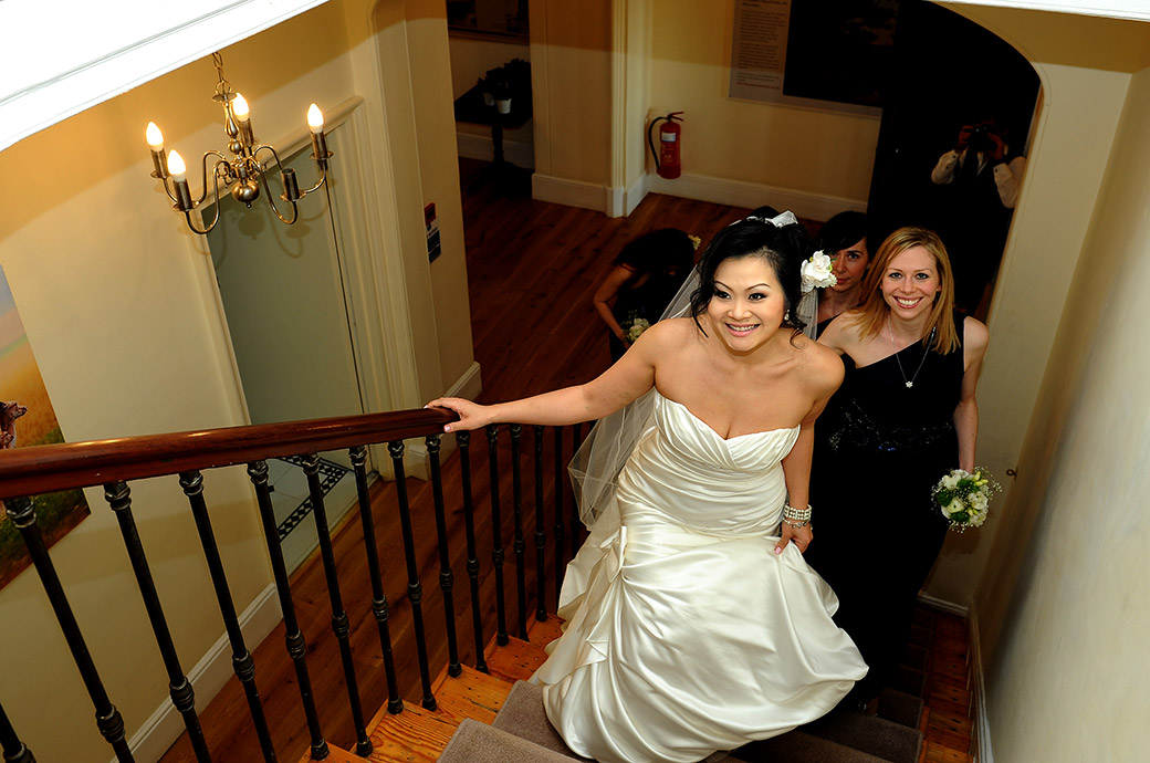 An excited Bride captured in this wedding picture as she ascends the stairs at Surrey wedding venue Pembroke Lodge on the way for her Russell Suite marriage ceremony