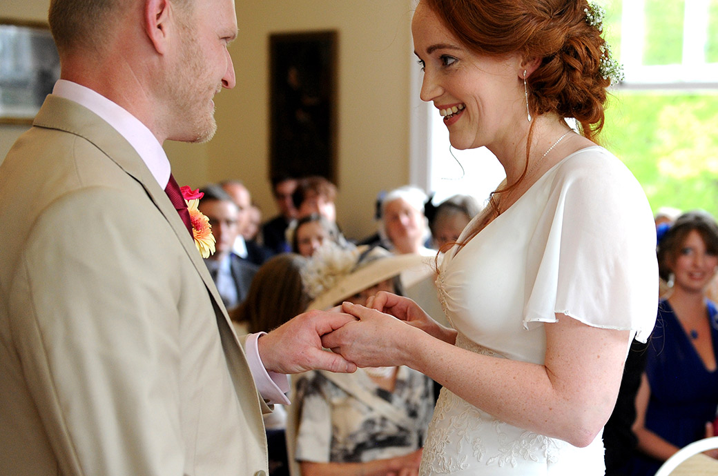 A wedding photograph of a very excited Bride in Surrey wedding venue Pembroke Lodge's Russell Suite pushing the wedding ring onto her smiling Groom's finger