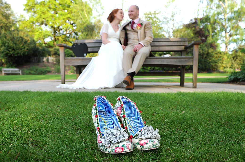 Bride and groom sit on a bench in the background chatting with the Bride's wonderful floral wedding shoes on show in the foreground at Pembroke Lodge Richmond Park Surrey