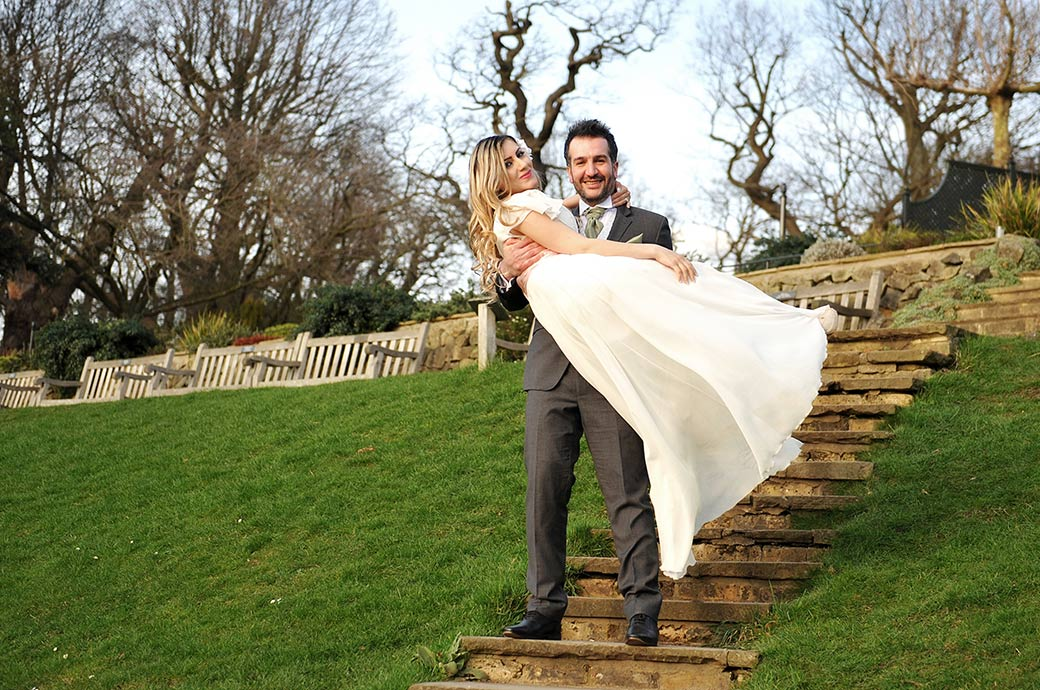 Proud smiling Groom captured at Surrey wedding venue Pembroke Lodge carries his lovely Bride down the steps to explore Richmond Park