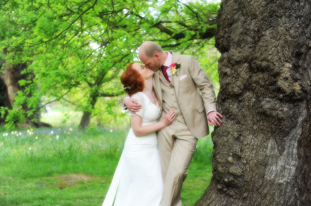 Lovely wedding photographs of Bride and groom at Surrey wedding venue Pembroke Lodge in Richmond Park romantically hugging and kissing by large ancient oak tree