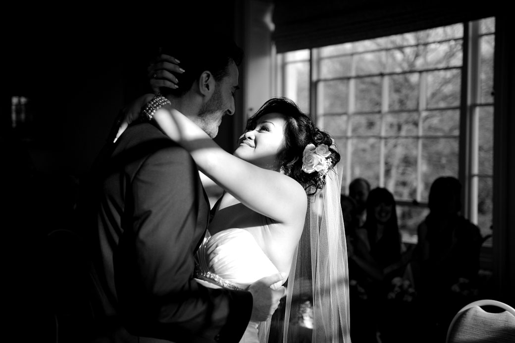The overjoyed Bride lovingly embraces her husband in this romantic wedding photo captured ar the popular Surrey wedding venue Pembroke Lodge in the intimate Russell Suite