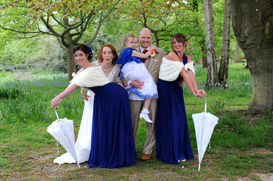 Groom joins in with his Bride and bridesmaids at Surrey venue Pembroke Lodge in Richmond Park for some fun wedding photography poses out on the lawn by the trees
