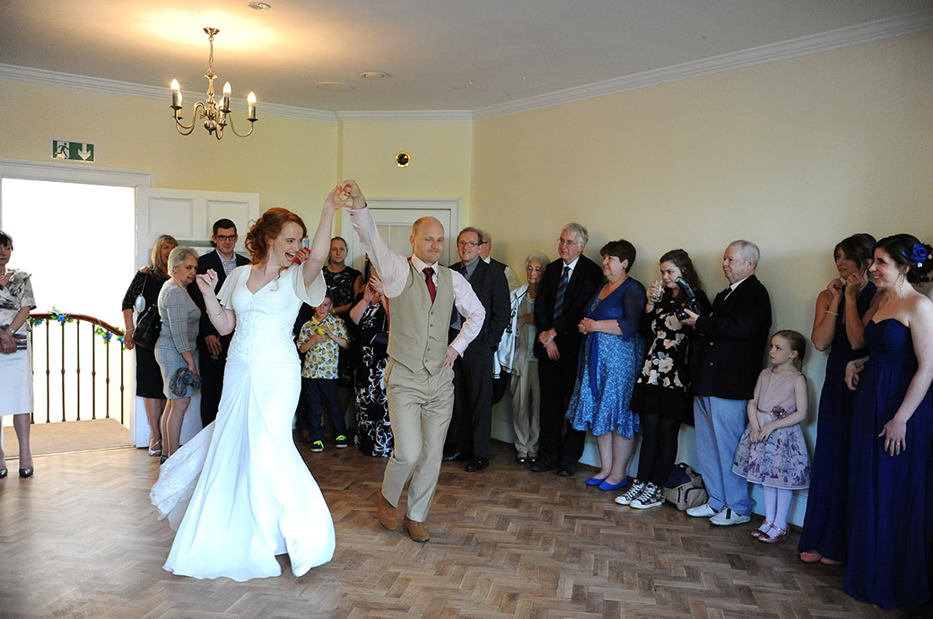 Groom in action at Surrey wedding venue Pembroke Lodge in Richmond Park with his hand on hip expertly leads his laughing Bride down the middle of the floor in ceilidh dance