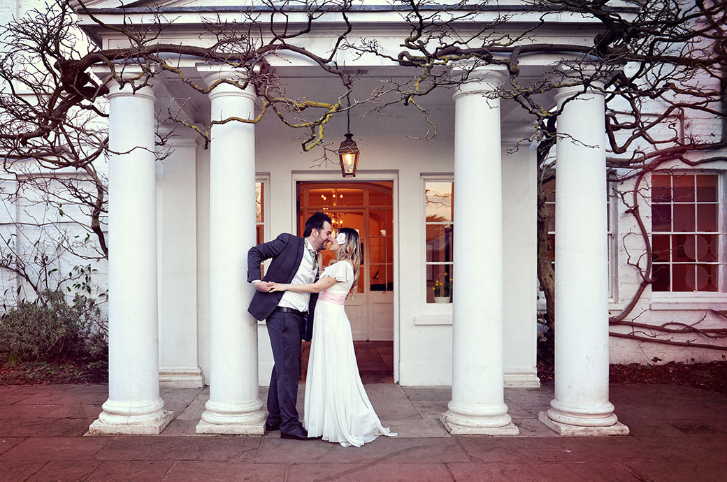 Groom captured in the pillared front entrance to Surrey wedding venue Pembroke Lodge in Richmond Park as he pulls his Bride in for a romantic embrace and kiss