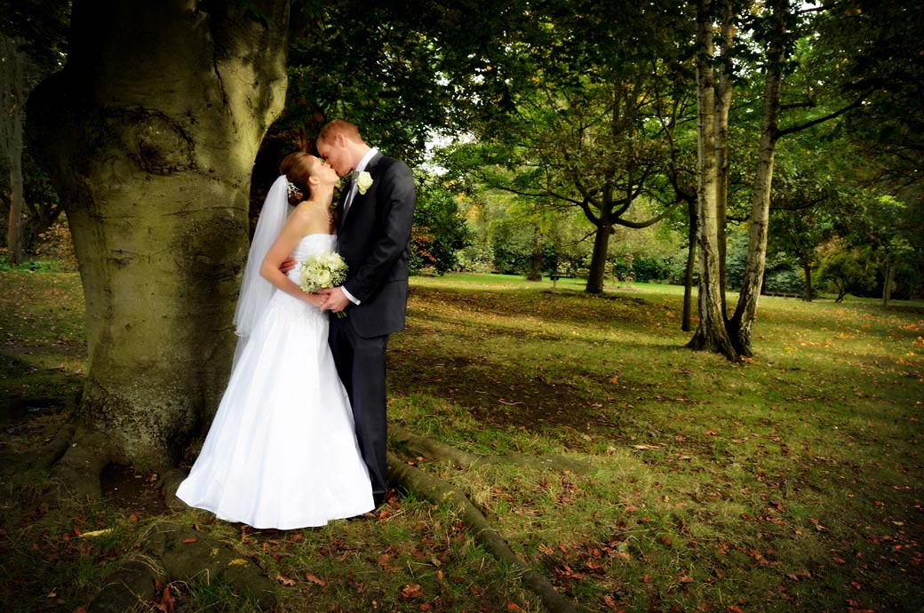 Beautifully romantic wedding picture of two newly-weds kissing amongst the trees taken at Pembroke Lodge by Surrey Lane wedding photographers