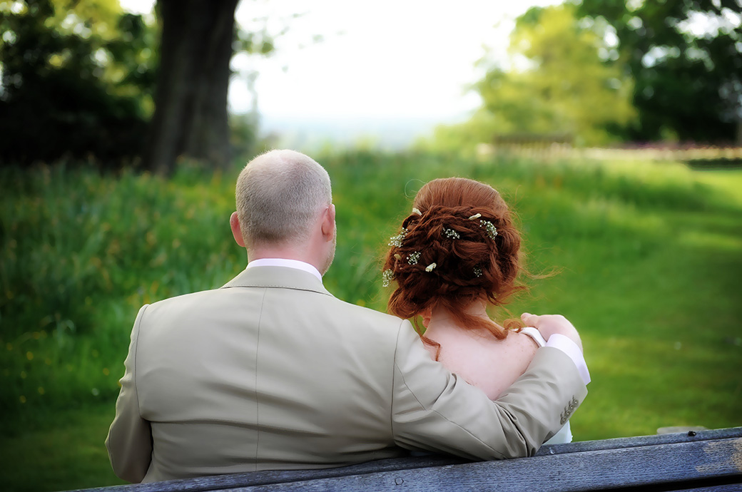 Romantic wedding photograph taken in Richmond Park at Surrey wedding venue Pembroke Lodge of a Bride and groom sitting on a park bench enjoying the lovely view
