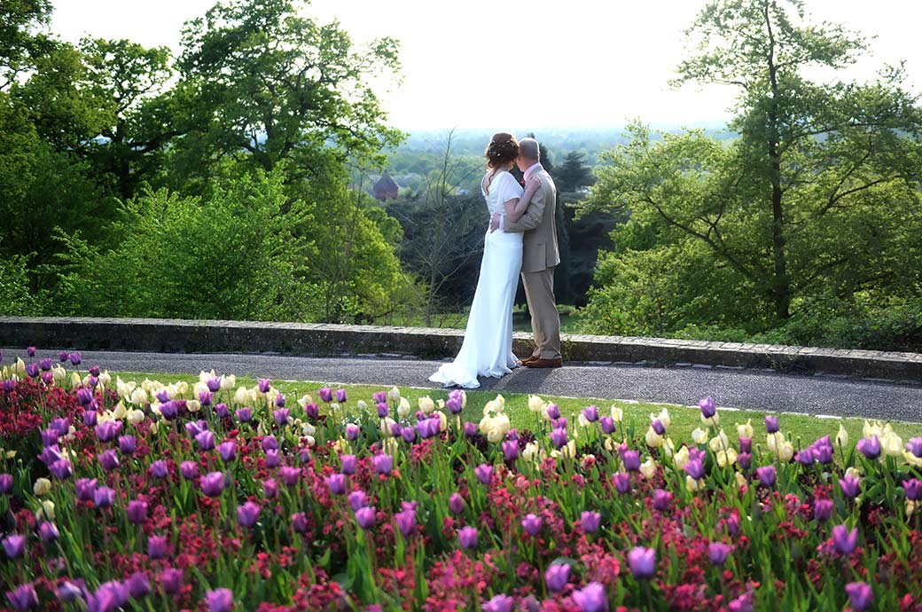 Bride and groom at Pembroke Lodge Surrey standing beyond a bed of bright tulips with arms touching each other as they survey the beautiful Richmond Park views towards London