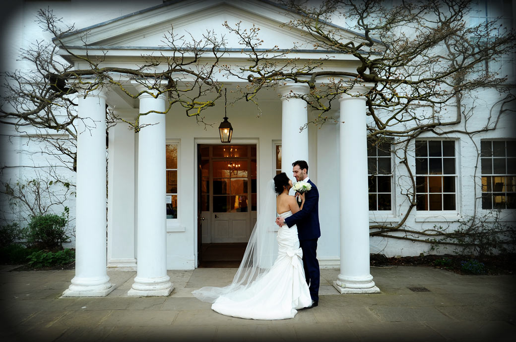 A time to reflect as the newlywed couple stand together arm in arm by the columned entrance of the beautiful Pembroke Lodge in Surrey with its stunning Richmond Park setting