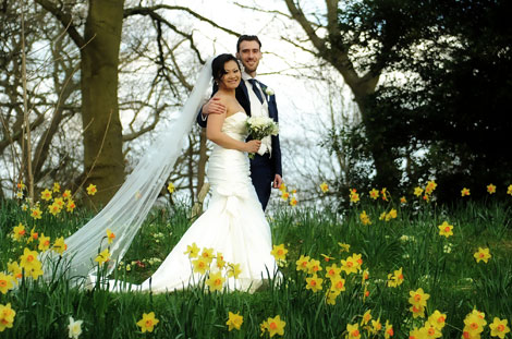 Time for a relaxed newlywed couple to walk through the daffodils in the woods in Richmond Park after getting married at Pembroke Lodge a uniquely placed Surrey wedding venue